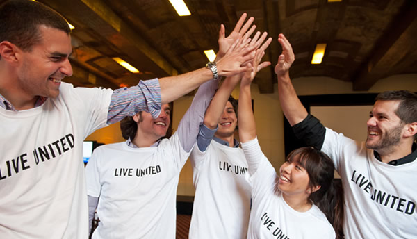 People in LIVE UNITED shirts high five